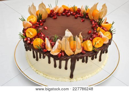 Isoalted Birthday Cake With Chocolate Icing And Citrus Decoration. Tangerine Cake, With Pomegranate