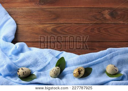Quail Eggs On Green Leaves On A Background Of Brown Wood And Blue Kitchen Cloth. Easter Table. Copy