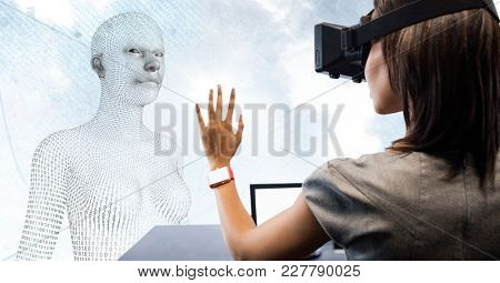 Digital composite of Woman in VR at desk in front of 3D female shaped binary code against sky and clouds