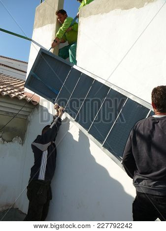 Alora, Spain - December 15, 2011: Men Lifting Steel Staircase Into Position In Village House, Andalu