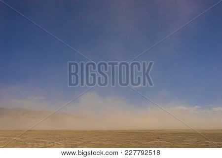 Sand Blows Over Flat Desert
