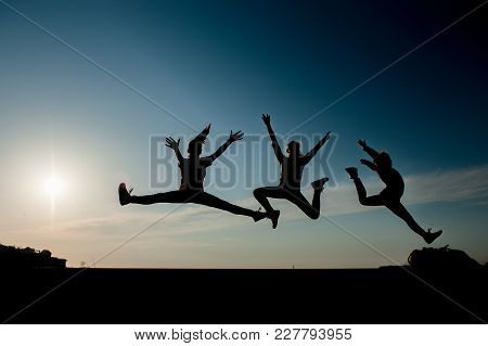 Three Silhouettes Of Jumping Athletic Teen Girls On Blue Sky Background At Sunset