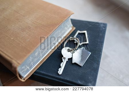 House Key And Keychain In The Form Of Homes Lies On Wooden Boards. Concept For Real Estate, Moving H