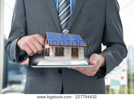 Digital composite of panels on the roof houses on tablet of the businessman