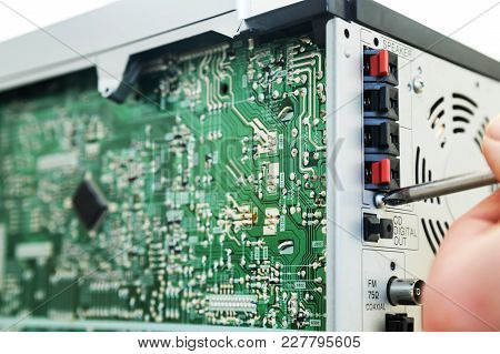 A Man Is Using A Screwdriver To Open The Music System.
