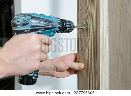 A Man Is Installing A Hook For Clothes. He Is Using A Screwdriver To Fix The Bracket Hook.