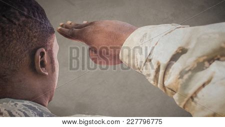 Digital composite of Back of soldier saluting against brown background with grunge overlay
