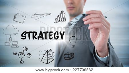 Digital composite of Business man mid section with marker behind strategy doodles against blurry grey wood panel