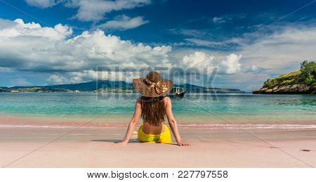 Rear view of a young woman with straw hat looking at an idyllic view while sitting on the sand at Pink Beach in Komodo Island, Indonesia