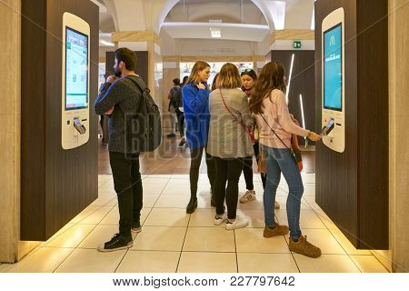 ROME, ITALY - CIRCA NOVEMBER, 2017: customers use self-ordering kiosks at McDonald's restaurant in Rome.