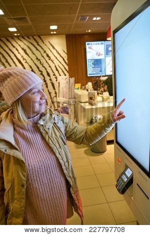 ROME, ITALY - CIRCA NOVEMBER, 2017: caucasian woman use self-ordering kiosk at McDonald's restaurant in Rome.
