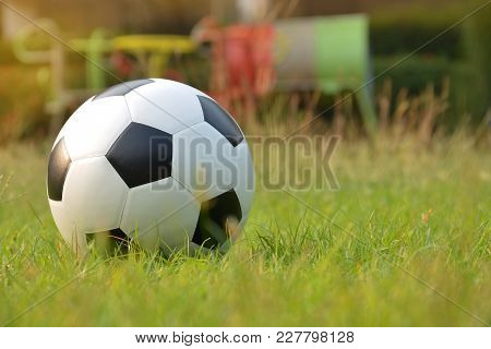 Football Or Soccer Ball On Green Grass With Morning Sunlight And Playground Background Background,ou