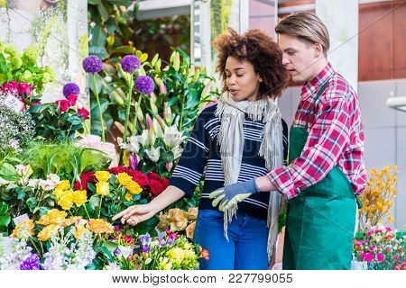 Beautiful Latin American woman buying freesias at the advice of a helpful and handsome vendor in a modern flower shop