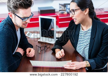 Man at optician shop getting advice from sales woman