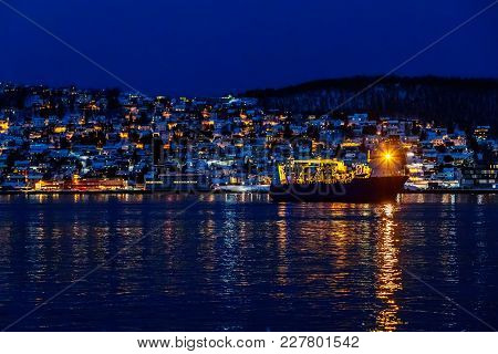 Cargo Transport Ship Turns Around In Dock Against Seaboard Town Lights. Mountains. Dark Time Of Day.