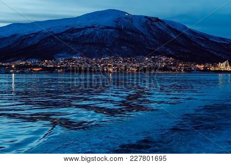 View Of Lights Of Coastal City From Sea Bay. Dark Time Of Day. Mountains In The Background. Low Key