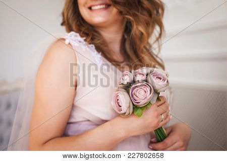 Young Happy Pregnant Girl With Curly Hair In Long Elegant Dress Holding Bouquet Of Flowers In Studio