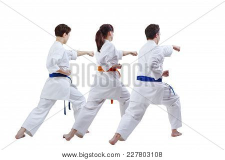 Two Women And A Man In Karategi Are Training A Punch With Their Hand