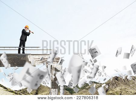 Young Engineer In Suit And Helmet Looking In Spyglass While Standing Among Flying Papers On Broken B