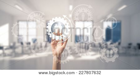 Close Of Woman Hand Touching Gears On Screen With Palm And Office At Background