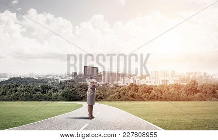 Business Woman In Suit With Tv Instead Of Head Keeping Arms Crossed While Standing On The Road With