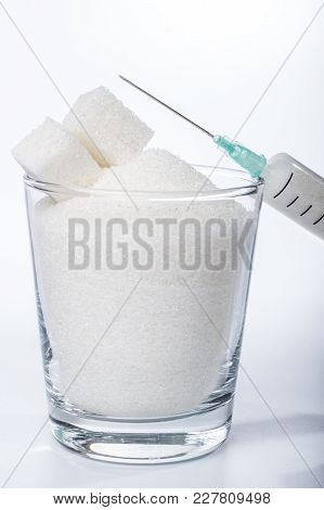 The Syringe Leaning Against The Glass With Sugar
