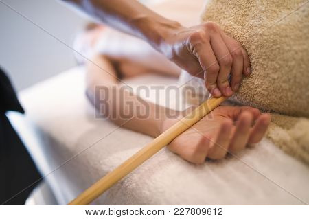 Massage Therapist Using Wooden Tool To Massage Patient In Saloon