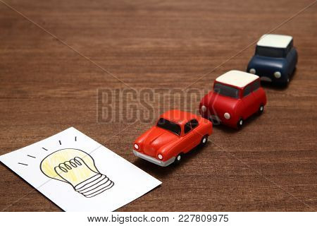Handwritten Bulb Illustration And Miniature Cars On Wood. Electric Car Concept.