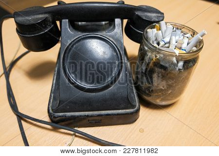 Vintage Phone And Dirty Jar With Cigarette Butts On The Table