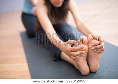 Close Up Of A Deep Stretch Yoga Practice: Cute Girl Reaching Out To Her Feet Stretching On A Yoga Ma