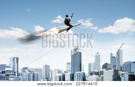 Conceptual Image Of Young Businessman In Suit Flying On Rocket With Modern Cityscape With Skyscraper