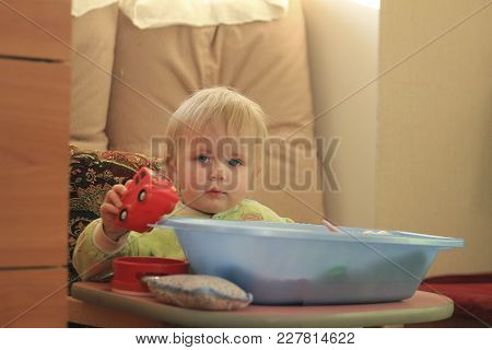 Portrait Of A Little Blue-eyed Blonde Girl With Her Toys At Home, Close Up
