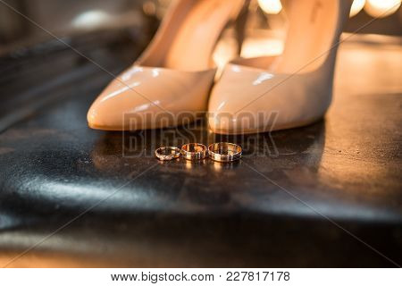 Golden Wedding Rings And Engagement Ring Lie On The Black Metal. Near Standing Fashion Beige Shoes O