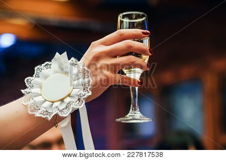 Woman's Hand Lifting A Glass Of Champagne Up