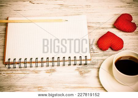 Coffee Cup Notepad Pencil And Two Red Hearts On Wooden Surface