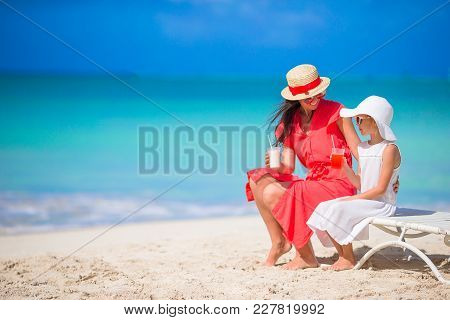 Mom And Daughter Rest On Beach Chairs