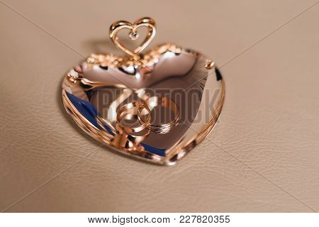 Gold Traditional Wedding Rings On A Beautiful Stand With Reflection
