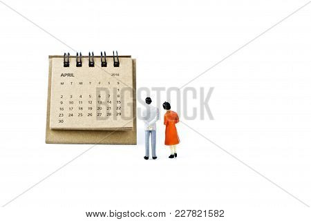 April. Two Thousand Eighteen Year Calendar And Two Miniature Plastic Figures. Man And Woman On White