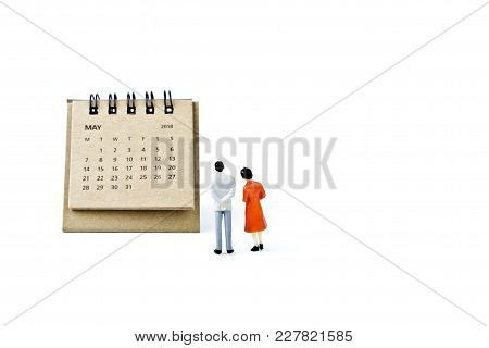 May. Two Thousand Eighteen Year Calendar And Two Miniature Plastic Figures. Man And Woman On White B