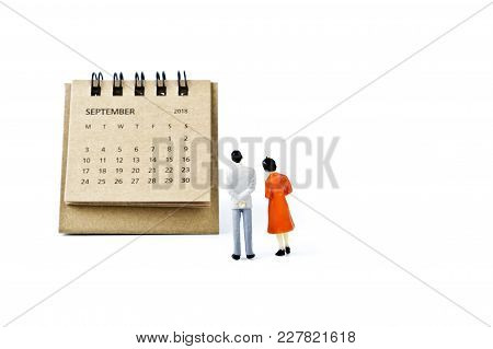 September. Two Thousand Eighteen Year Calendar And Two Miniature Plastic Figures. Man And Woman On W