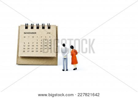 November. Two Thousand Eighteen Year Calendar And Two Miniature Plastic Figures. Man And Woman On Wh