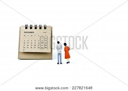 December. Two Thousand Eighteen Year Calendar And Two Miniature Plastic Figures. Man And Woman On Wh