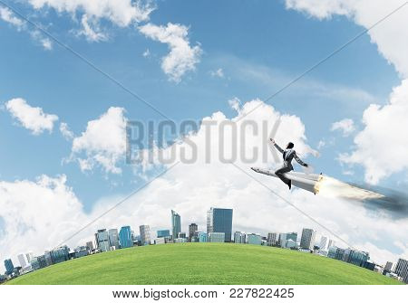 Conceptual Image Of Young Businessman In Suit Flying On Rocket With Cityscape And Blue Sky On Backgr