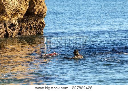 Underwater Hunter, On The Surface, Adjusts The Buoy With Harpoons And Crossbows.