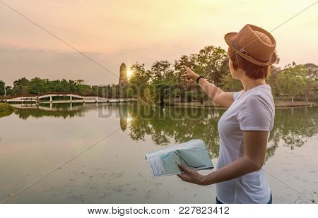 Tourist Woman Holding Map And Pointing To Ancient Place Sightseeing Direction.
