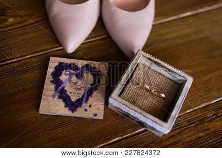 Two Wedding Golden Rings In The Wooden Box. Near Standing Bridal Pink Shoes.