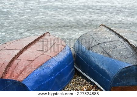Two Fishing Boats Turned Upside Down On The Beach By The Lake