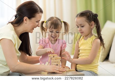 Family Mom And Daughters At The Table Playing Board Game
