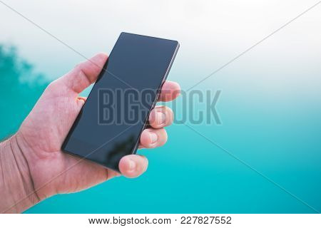 Using Mobile Phone By The Swimming Pool, Male Hand Holding Smartphone With Blank Screen As Copy Spac