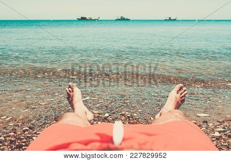 Man Relaxing On The Beach With Feet Bathing In The Water